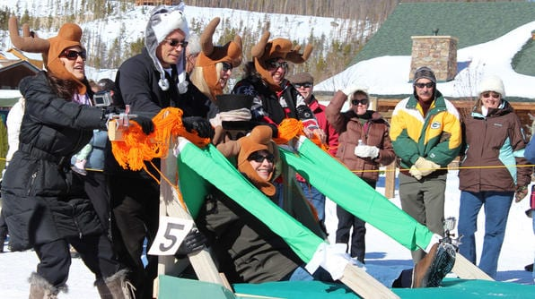 Anthony Melchiorri and Blanche Garcia pushing bed sled at Winter Carnival