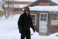 Anthony walks through the snow in front of the Western Riviera cabins.